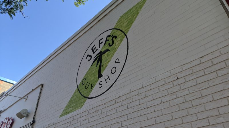 Jeff's Guy Shop logo painted on a brick wall on Brant St.